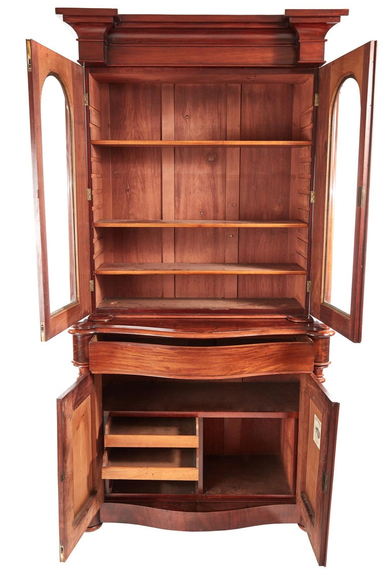 This is a quality 19th century Victorian antique mahogany bookcase. The upper section having an attractive shaped cornice over a pair of glazed doors with shaped mouldings and turned columns. The doors open to reveal an interior with adjustable
