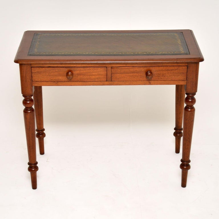 Antique Victorian mahogany writing table with a tooled leather writing surface. It's in very good original condition and dates to circa 1860-1880s period. There are two drawers with turned bun handles and it sits on turned legs.