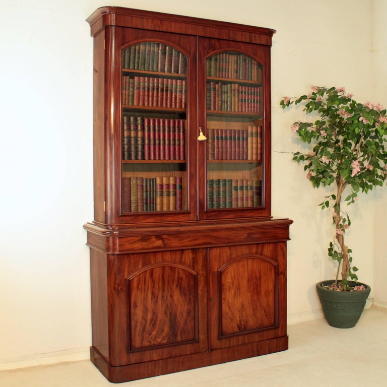 An attractive Victorian mahogany bookcase dating to circa 1870, with a moulded cornice above a pair of glazed doors enclosing three adjustable shelves, the projecting base with a concealed drawer and two panelled cupboard doors, all standing on a