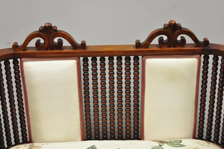 Antique Victorian mahogany upholstered Victorian spool spindle bench loveseat. Item features