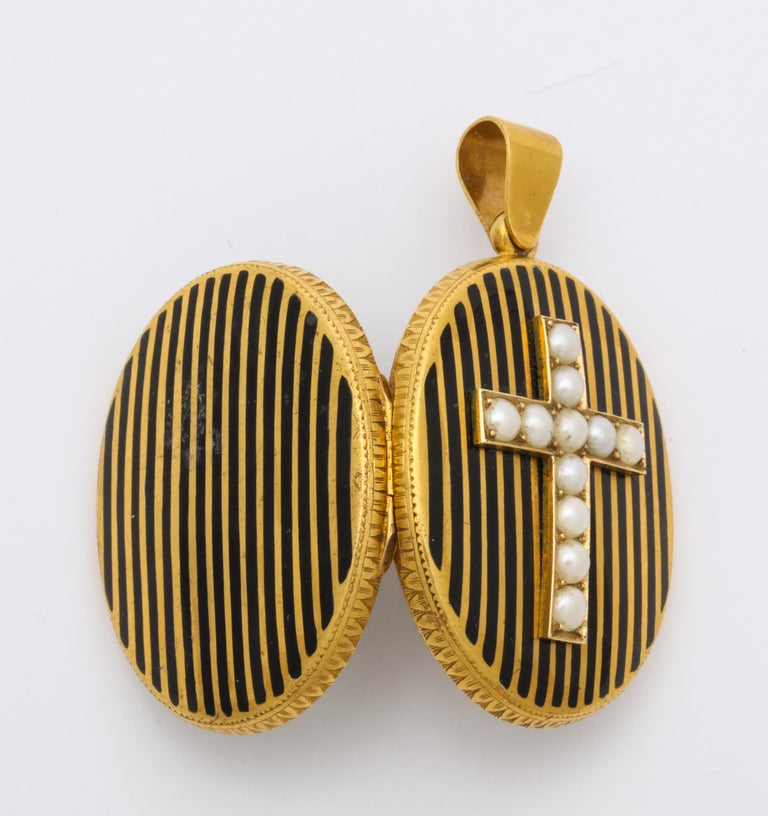 Midpoint on this 18 kt oval locket, set above vertical black enamel stripes, is a cross of radiant natural pearls. The pearls are perfectly matched with no loss to the nacre, the pearlescent layer on the top of the bead. Both front and reverse are