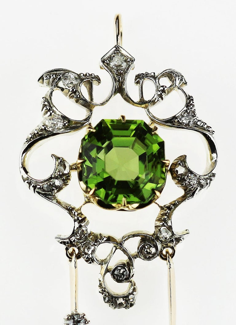 Antique, Victorian  Peridot and diamond pendant/brooch set in 18K yellow gold and silver, with detachable brooch fitting. 1 x Cut corner rectangular Peridot, approximate weight 3.3 carats 19 x Old European and Rose cut diamonds, approximate total