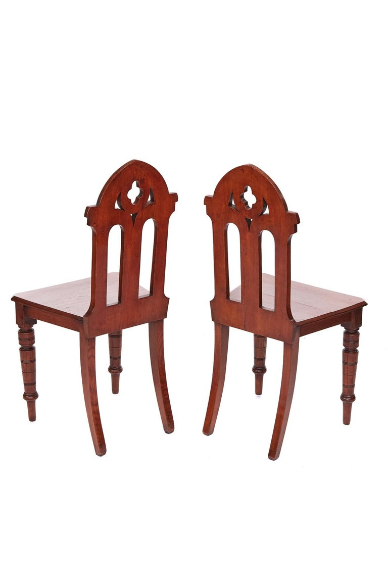 Antique Victorian quality pair of oak gothic hall chairs having carved oak backs with shaped turned legs to the front and outswept legs to the back. Lovely color and condition.