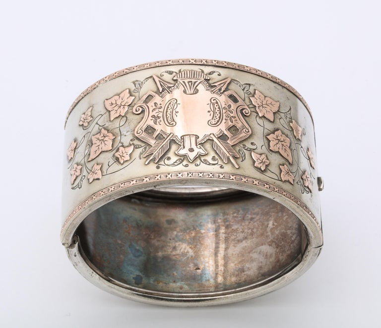 A refined and rare silver Victorian Cuff, elegant and grand, is floridly engraved with a gold washed shield and ivy leaves. The shield is so strong that it had to have been that of an aristocratic family with strong family ties, shown by the ivy