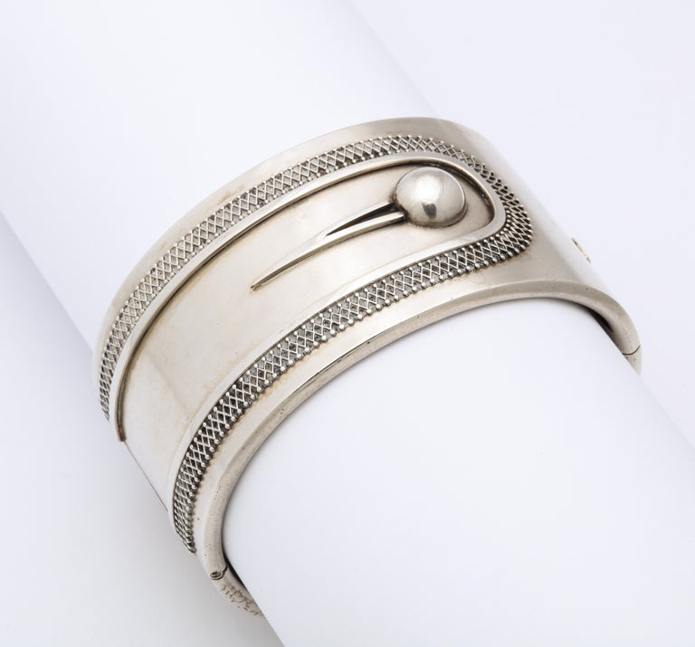 The simplicity of this silver button cuff bracelet makes the contrast in texture a standout.  Diamond formed architectural wire work surrounds the button strap. I fell in love with the positive negative space that for some reason gives pleasure
