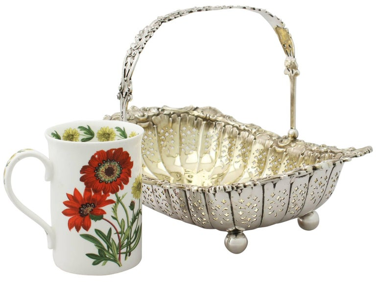 A fine and impressive antique Victorian English sterling silver swing handled basket by James Dixon & Sons Ltd; part of our ornamental silverware collection.  This antique Victorian sterling silver basket has a rectangular rounded form onto four
