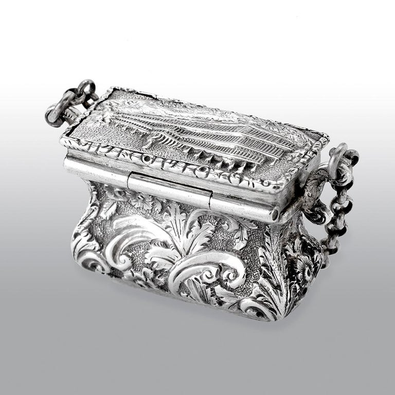 A fine antique Victorian silver Castle-top vinaigrette, has a waisted bag form, chased foliate scroll decoration on a matted background, the hinged cover with a view of the Crystal Palace great exhibition 1851 the fine silver gilt interior with a