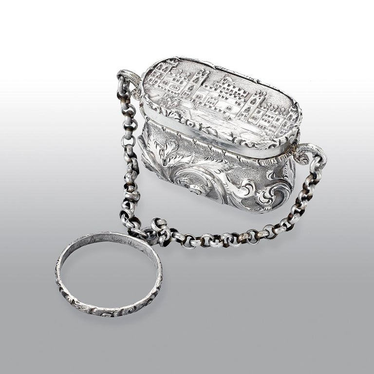 A fine antique Victorian silver castle-top vinaigrette, has a waisted bag form, chased foliate scroll decoration on a matted background, the hinged cover with a view of the castle with the round tower, the fine silver gilt interior with a pierced