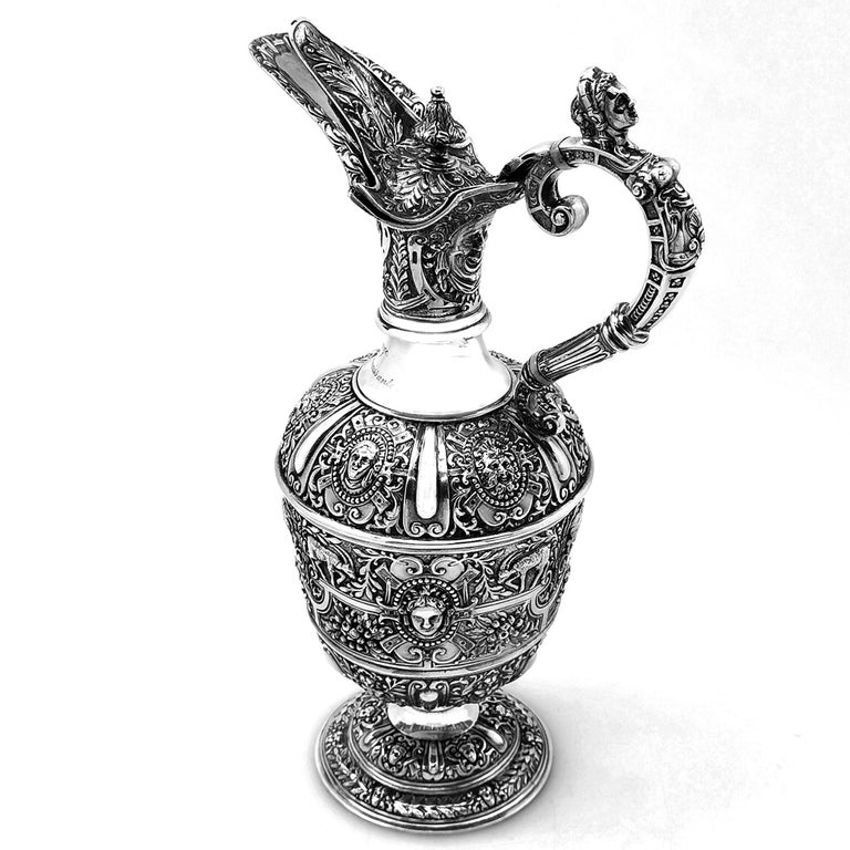 A beautiful Classic Antique Victorian solid Silver Jug in the traditional 'Cellini' design. The Jug features rich, detailed patterning and a figural handle and thumb piece. The Jug has a small engraving on the neck.  Made in London in 1889 by JN