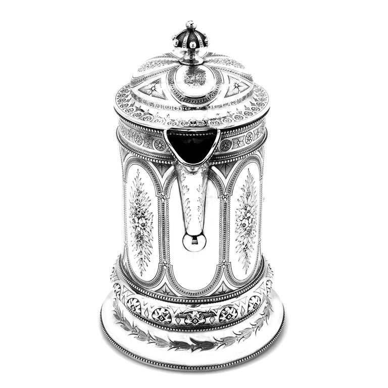 A magnificent antique Victorian solid Silver Jug decorated with a rich, ornate floral engraved design. The engraved design on the Jug extends from the body and onto the spout, handle and domed lid. One of the engraved cartouches is left blank and is