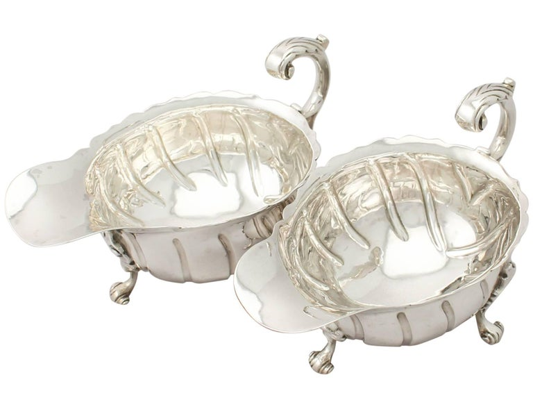 A fine and impressive pair of antique Victorian English sterling silver sauceboats; an addition to our dining silverware collection.  These fine antique Victorian sterling silver sauceboats have an oval rounded form.  The surface of each silver