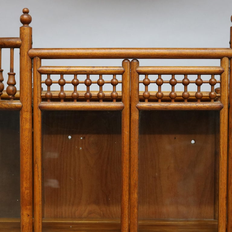 An antique Victorian hanging demilune wall display cabinet offers oak construction with stick and ball gallery over double curved glass door cabinet with shelved interior and stick and ball base, c1900  Measures: 31.75