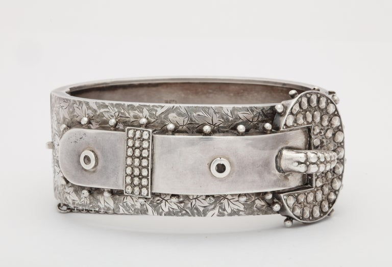 A spark of edginess, along with the romance of ivy,  a budded vine that weaves along the bracelet front, plus its buckle motif and terrific texture, all show the masterful work of the English silversmith in the late Victorian period. Silver studs
