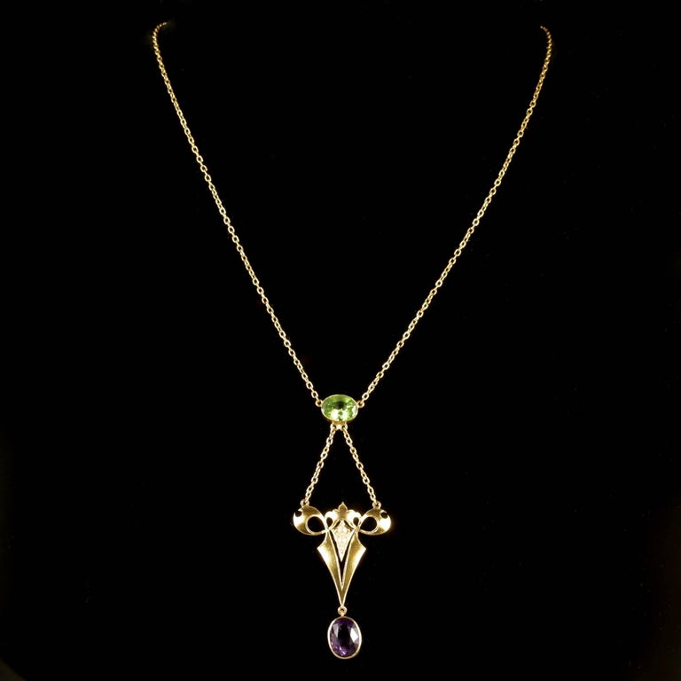 This fabulous 15ct Yellow Gold Victorian Suffragette necklace is Circa 1900.  The beautifully designed necklace is adorned with a Peridot, leading down to 3 Pearls in a Gold gallery, and a Amethyst dropper. This combination of gemstones represent