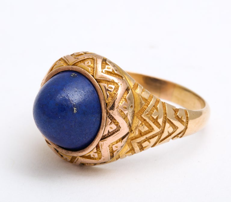 A two carat plus dome of Lapis Lazuli has characteristic flecks in the stone and looks like the clear blue of the night sky. The ring cut is know as a sugarloaf as it rises upward from the shank. A stunning geometric shank in 14 Kt.emphasizes the