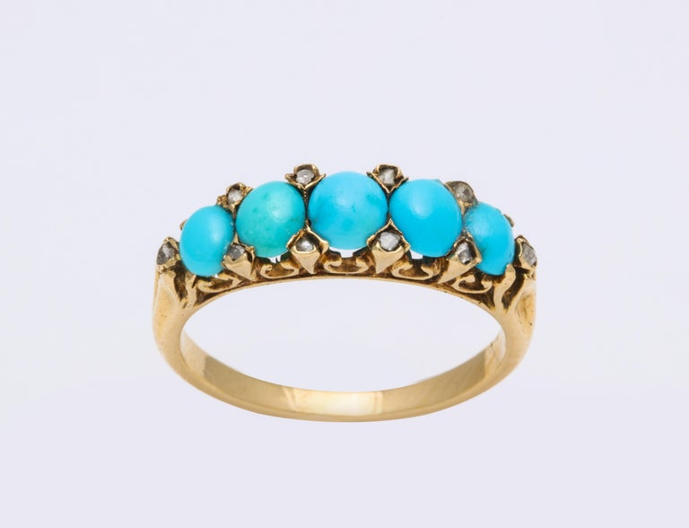 A pristine band of bright, beautifully matched oval turquoise from Persia are sparked by the tiny diamonds interspersed in their lovely architectural 15 kt gold setting. Regardless of theIr small size, the diamonds sparkle in the light and give the