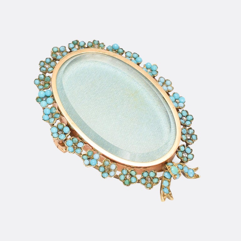 A beautiful antique locket, with fittings for wear either as a brooch or a pendant. The bevelled glass front is accessed from the back, and bordered by intricately worked forget-me-not flowers – each one set with five turquoise cabochon petals and a