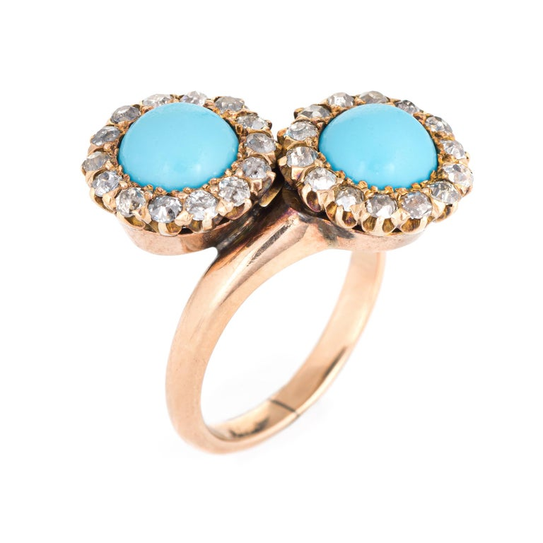 Finely detailed antique Victorian turquoise & diamond double halo ring (circa 1880s to 1900s), crafted in 14 karat yellow gold.   Cabochon cut turquoise measures 7mm (each), accented with 28 estimated 0.05 carat old mine cut diamonds. The total