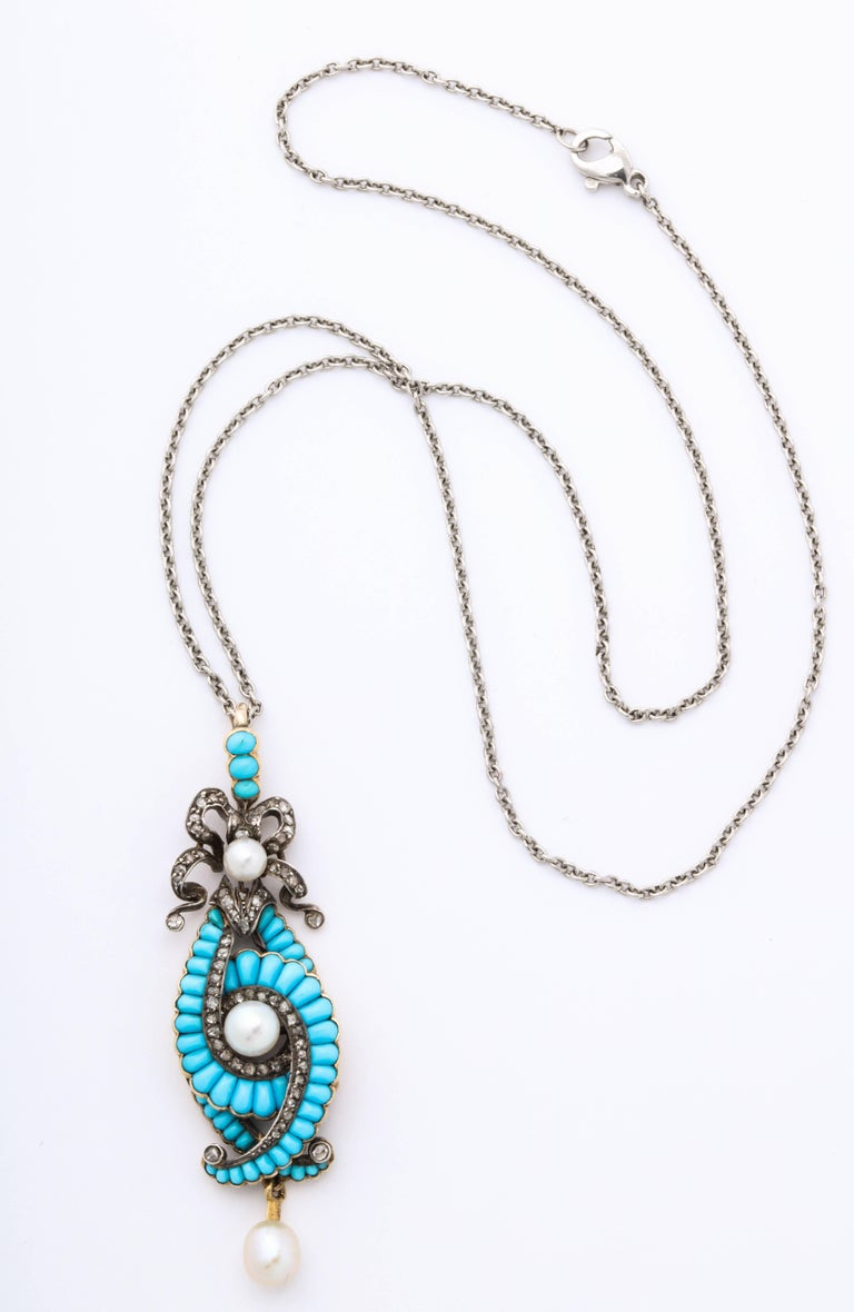 Perfect turquoise in pellet shaped cushions, are set in crossing scrolls and joined by scrolls of .70 cts rough cut antique diamonds repeating  their form beneath a frilly diamond bow. Unquestionably unusual and feminine, an addition of lustrious