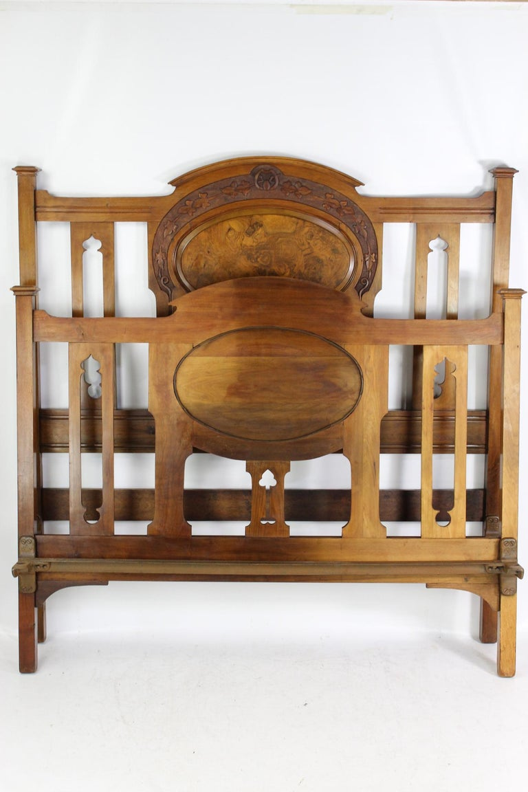 A charming antique Victorian Arts & Crafts carved walnut double bed dating from circa 1890. The headboard and footboard in a richly figured walnut frame with attractive foliate carved top rail and central burr walnut panel above vertical slats with