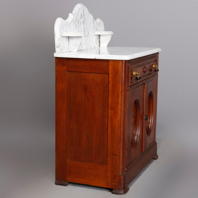 An antique Victorian washstand offers beveled marble-top with shaped backsplash having candle stands surmounting walnut and burl case with frieze drawer and double door lower cabinet, circa 1880  ***DELIVERY NOTICE – Due to COVID-19 we are employing