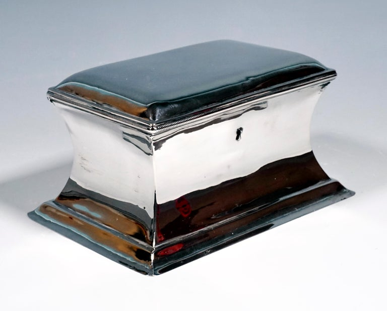 Rectangular basic shape, smooth design of the concave inwardly curved walls, slightly cambered hinged lid with cord strap. Lock present, no key. Finest handwork of simple elegance by the Viennese silversmith Anton Weichesmüller.  Branded by the