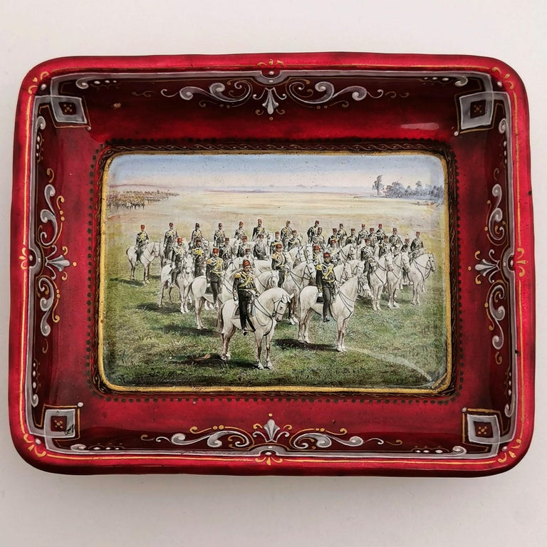 A lovely Antique Viennese Enamel Dish /Pin Tray featuring a wonderful enamel design showing a Turkish Army on Horse Back in a field. The sides of the Tray and the exterior are covered in a rich iridescent red with a white and gold border on the