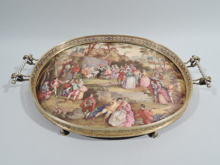 Austrian Rococo silver gilt and Viennese enamel tray, ca 1880. Oval enamel well depicting village green peopled with harp-strumming, minueting, love-making gentle folk. A flower wreath is suspended above a man and woman seated at a table with a