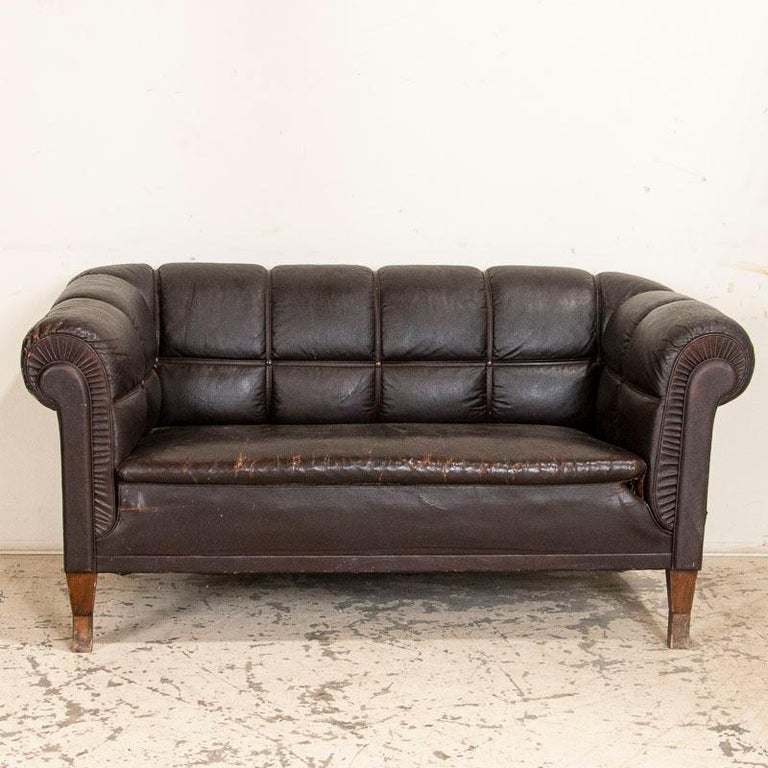 The rolled arms and back of this vintage brown leather sofa are accented by leather strips which adds to their visual appeal. There is age related wear to the dark brown leather which is more extensive to the seat cushion and arms, also separation