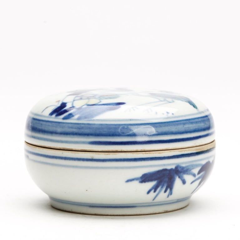 A fine antique or vintage Chinese porcelain lidded box of rounded form decorated with a figural scene of a man and child, the child feeding a bird decorated in Wucai glazes. The inner box has a further figural design and the box stands on an