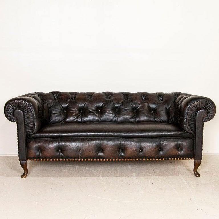 There is a unique allure to an old vintage leather sofa, as if all the conversations held on it over many years still draw us in. This handsome 7' Chesterfield sofa has a rich tobacco vintage leather, cracked and worn in all the right places. The