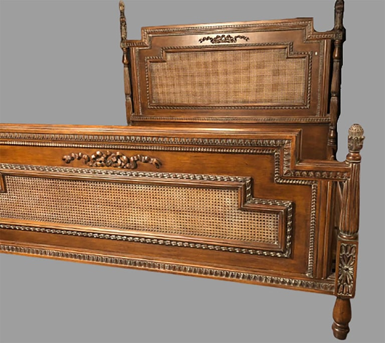 Antique walnut carved king sized bed. Headboard, foot-board and side-rails. This vintage finely carved and cane headboard and foot-board are simply stunning. Each having a ribbon and tassel carved front with pineapple carved posts, the set with cane