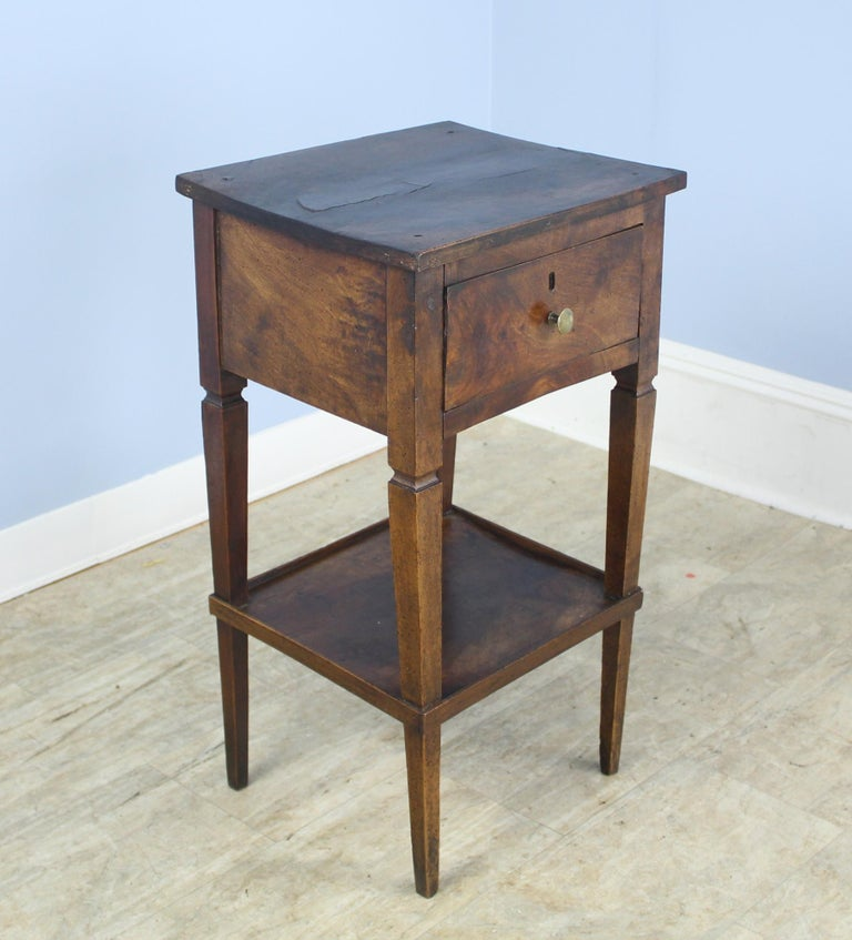 A lovely occasional table in dark patinated walnut. The top shelf is thick and has lovely walnut grain with a slight bow. The lower shelf adds a decorative element, and has little galleries to keep items from slipping off. Some distress and a