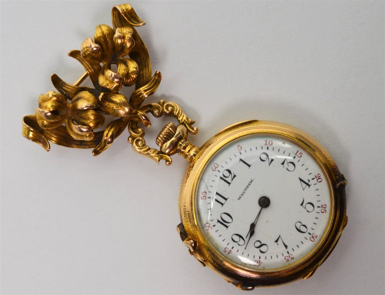 Early 20th century craftsmanship is evident in this charming circa 1901 Ladies Gold Watch Brooch made by famous American watchmakers, Waltham Watch Co.  In fourteen carat 14k yellow gold with a beautiful antique patina, the decorative watch case is