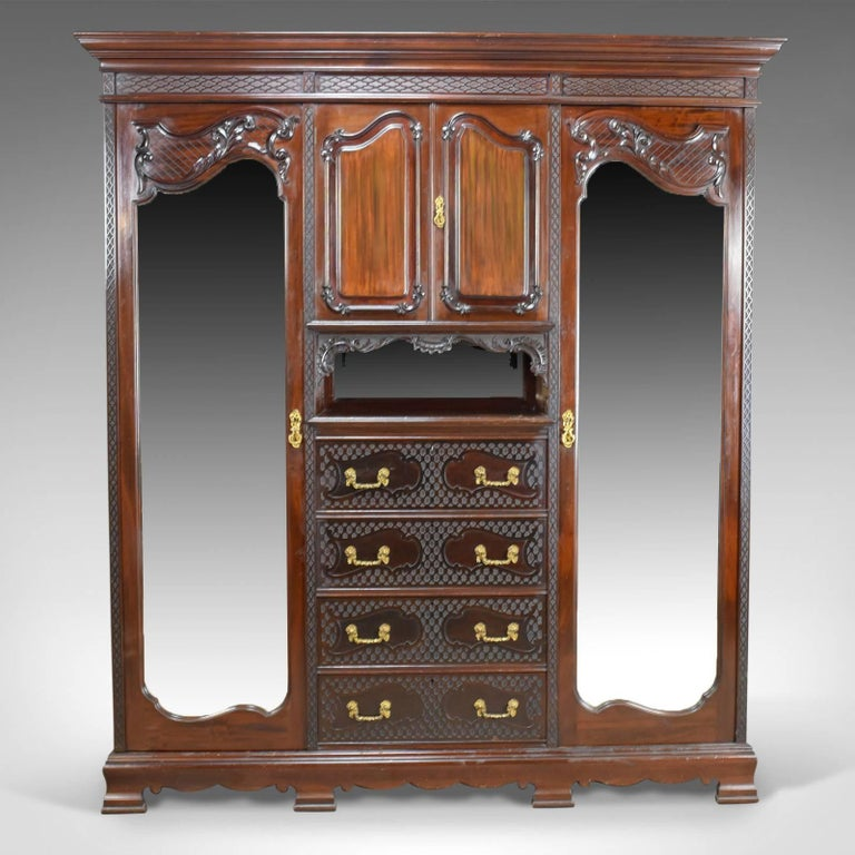 This is an antique wardrobe in carved mahogany, an English compactum dating to the Edwardian period, circa 1910.