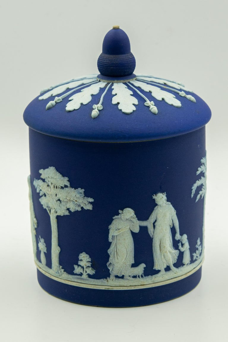 Antique dark cobalt blue dip Wedgwood jasper ware biscuit barrel featuring a sprig moulded decoration which shows neoclassical figures. The scene contains women, children and animals among trees and flowers. The lid is decorated with a wide band of