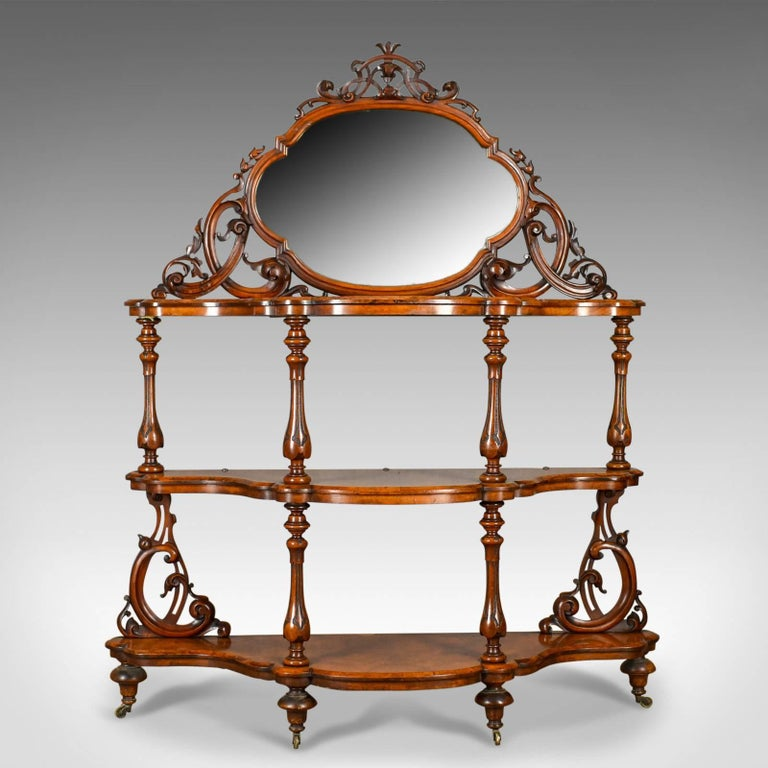 This is an antique whatnot, an Irish, burr walnut, three tier, mirror-back, display Stand by the highly regarded Robert Strahan & Co. firm of Dublin, Ireland. Dating to the early to mid-19th century, circa 1840.  Of exceptional quality befitting