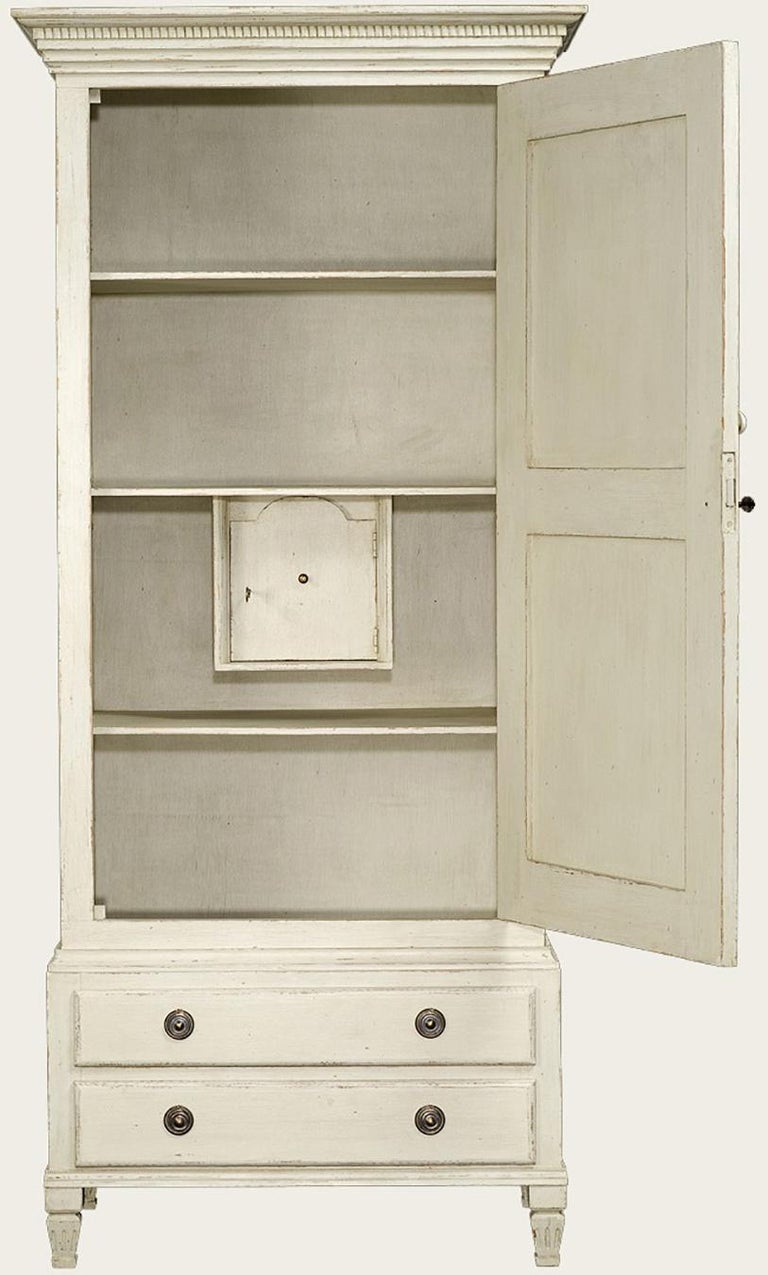 Wonderful antique white, distressed painted wardrobe / cabinet with shelves, two drawers below, and a safe inside is perfect for any bedroom, hallway, living room or even kitchen. Hand carved and painted with a warm off-white color with solid wood
