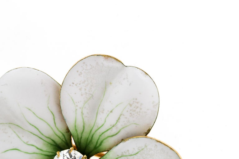 Antique Art Nouveau 18k gold white enamel flower pin set with an Old European cut diamond, circa 1900. The bold white petals has green enamel details creating the realistic quality of the flower. There is a small gold stem at the bottom of the