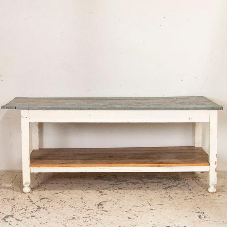 What a fun find! This vintage farm table has the original zinc top and a lower shelf, indicating it was used as a type of work table in its former life. The zinc, which has great aged patina, wraps around 3 of the four sides; as seen in the photos,