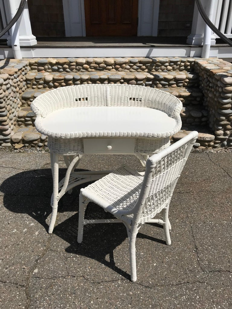 """Antique wicker desk and chair in fresh white paint. Desk measures: 39"""" by 24"""" and is 36"""" tall."""
