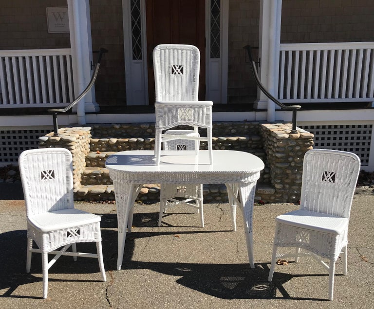 Antique wicker dining table and four chairs in fresh white paint. Solid wood top with woven reed skirt and woven legs on the table. Four matching woven reed chairs.