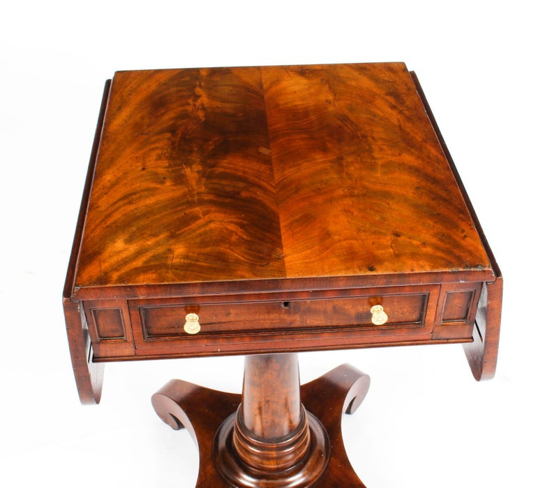 An exquisite antique William IV flame mahogany drop leaf work table, circa 1830 in date.  This beautiful work table has a useful frieze drawer with a paneled drawer front and features Y-pattern supports with a sturdy turned centre column and a