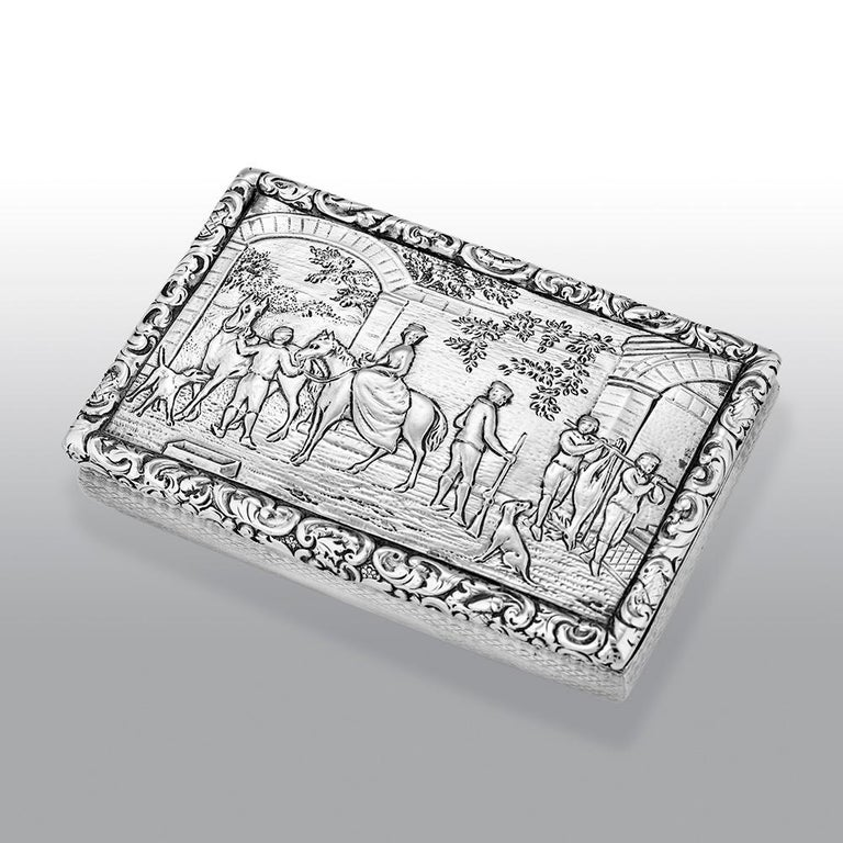 A fine William IV Scottish sterling silver snuff box of rounded rectangular form, the hinged cover depicting a fine village scene with horses, dogs and people in the courtyard, the sides and base engine-turned, the cover opening to reveal a gilt