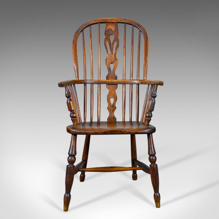This is an antique Windsor armchair, an English Victorian, country kitchen, stick back elbow chair in elm and ash dating to circa 1860.  Stunning chair in fine order throughout Classic pierced back splat above and below the arm bow Raked,