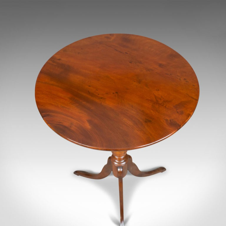 This is an antique wine table, a Regency, circular, side table in mahogany dating to the early 19th century, circa 1820.  Crafted in select stocks of quality mahogany Good color and grain interest in a lustrous wax polished finish Of quality