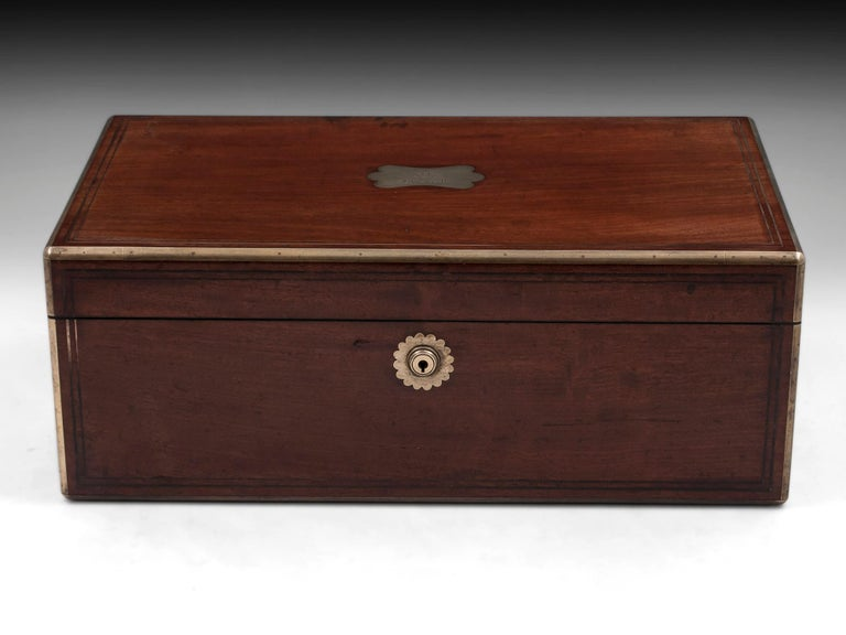 Antique brass bound mahogany writing box with double brass stringing, flush carry handles and shaped initial plate with an engraved coat of arms and the name John Scott. The interior features a burgundy leather writing surface with beautiful gold