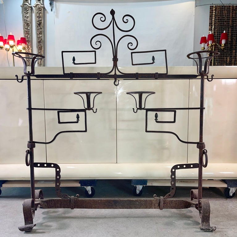 French 18th century fer forge lanier fireplace screen with two swing out arms and four baskets, leafy scroll decoration, rings and hooks for hanging utensils, standing on scrolled feet.  Reference: Les objets de la vie domestique: Ustensiles en