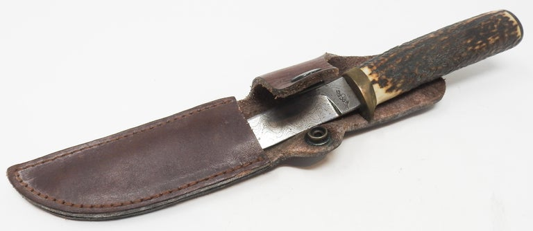Offering this handsome antler handle short knife with leather sheath. The sheath appears to have been handcrafted from a nice heavy leather. There is a spot to loop a belt through, and a button to snap and keep the knife in place. The antler handle