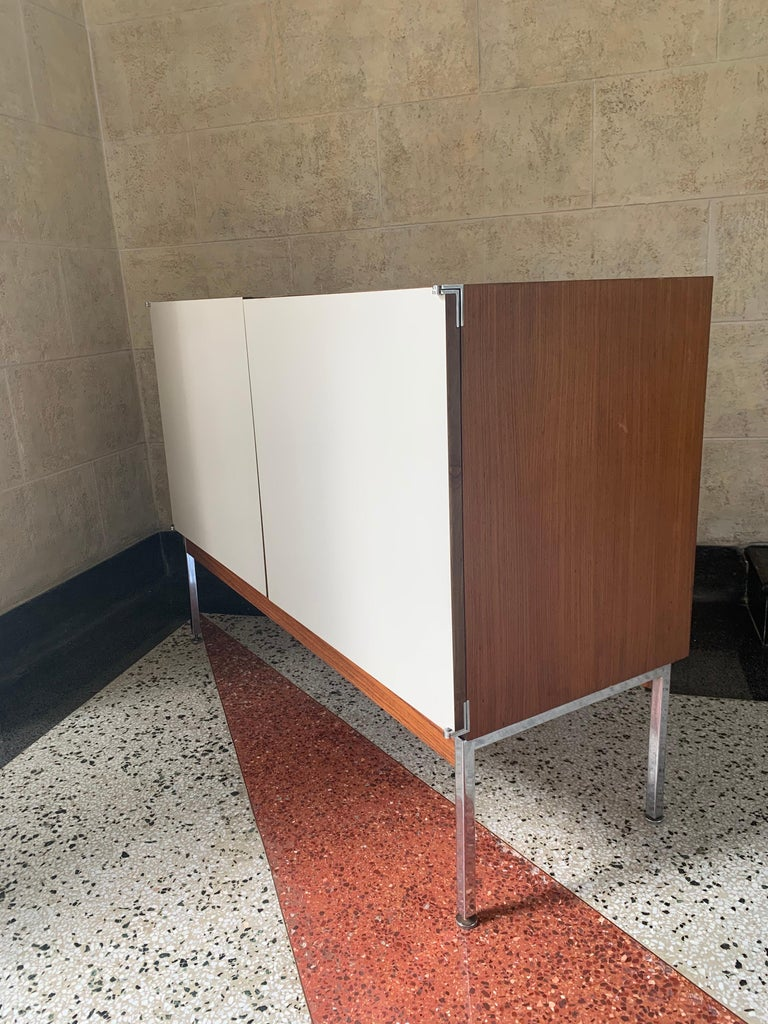 Exquisite original 2 door cabinet credenza or sideboard, rendered in rosewood case with light wood interior with 2 adjustable shelves and 2 matte white laminate doors, on a chrome-plated steel base, also has original wall mount brackets to be a very